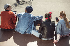 Teenagers group sitting sitting together and using digital devices Royalty Free Stock Images