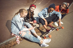 Teenagers group sitting sitting together and using digital devices Royalty Free Stock Photo
