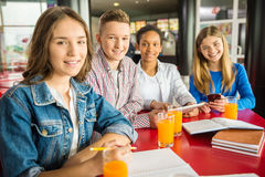 Teenagers. A group of teenagers sitting at the table in cafe, studying and drinking orange juice stock photo