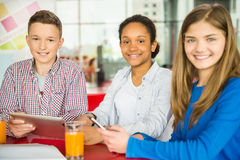 Teenagers. A group of teenagers sitting at the table in cafe, studying and drinking tea stock photo
