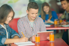 Teenagers. A group of teenagers sitting at the table in cafe, studying and drinking tea royalty free stock image