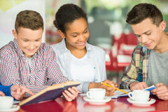 Teenagers. A group of teenagers sitting at the table in cafe, studying and drinking tea royalty free stock images