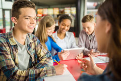 Teenagers. A group of teenagers sitting at the table in cafe, studying and using tablet stock photo