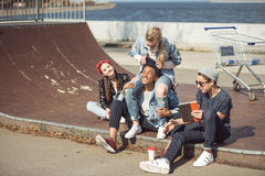 Teenagers group sitting together on the ramp and having fun Stock Photos