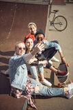 Teenagers group taking hipster selfie while sitting together at skateboard park Stock Photography