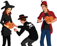 Teenagers in Halloween costumes carving faces on pumpkins Royalty Free Stock Photos