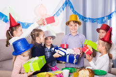 Teenagers handing gifts to birthday boy Royalty Free Stock Photos