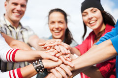 Teenagers hands on top of each other outdoors Stock Photo