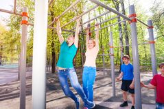 Teenagers hang on horizontal bar at sports ground Stock Photos