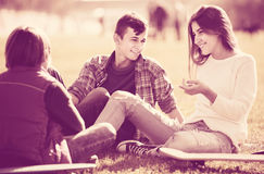 Teenagers hanging out outdoors and discussing something Stock Images