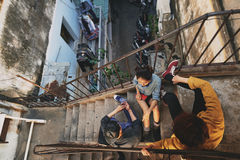 Teenagers Hanging out in Urban Slums. High angle view of stylish Asian teenagers hanging out in urban slums: they sitting on stairs of shabby apartment house and Royalty Free Stock Photo