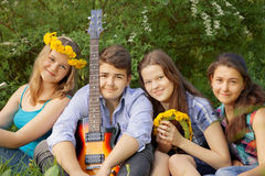 Teenagers have fun in the park, playing guitar, singing son Stock Image