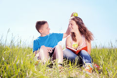 Summer portrait, children with apples. Teenagers have a rest on a green grass Royalty Free Stock Photography