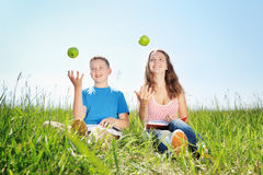 Summer portrait, children with apples. Teenagers have a rest on a green grass royalty free stock image