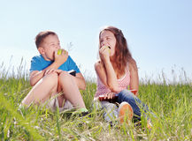 Summer portrait, children with apples. Teenagers have a rest on a green grass Royalty Free Stock Photos