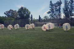 Bubble balls game. Teenagers having fun during a bubble bump game outdoors player team sport football adversary child risk shock people transparent inside royalty free stock photography