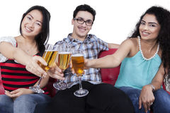 Teenagers having fun by drinking champagne. Multi ethnic people smiling at the camera while toasting champagne, isolated on white Stock Photography