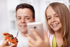 Teenagers having fun eating pizza and taking selfies royalty free stock photography