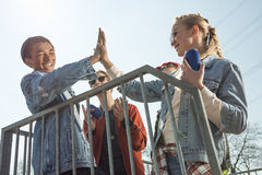 Teenagers having fun and giving highfive in skateboard park Royalty Free Stock Photography