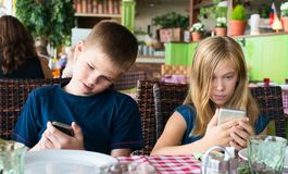 Teenagers having fun with mobile phones in cafe. Modern lifestyle and technology concept. Children sitting in restaurant and