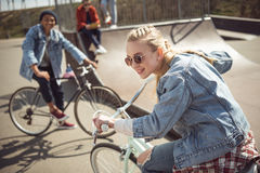Teenagers having fun and riding bicycles in skateboard park. Bike riding city concept royalty free stock photos