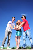 Teenagers holding hands. Portrait of three beautiful teenagers with their hands piled ontop of each other to signal unity and strength Royalty Free Stock Images