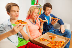 Teenagers holding pizza pieces and eating. Together sitting on white sofa at home Royalty Free Stock Photos