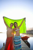 Teenagers holding towel on dock Stock Photo