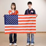 Teenagers holding up American flag Stock Photo
