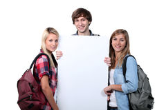 Teenagers holding up poster Stock Photo