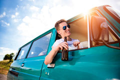Teenagers inside an old campervan, drinking beer, roadtrip. Teenagers inside an old campervan on a roadtrip, boy leaning out of window, drinking beer, sunny royalty free stock images