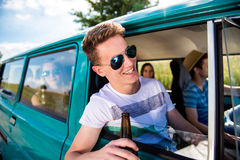 Teenagers inside an old campervan, drinking beer, roadtrip. Teenagers inside an old campervan on a roadtrip, boy leaning out of window, drinking beer, sunny royalty free stock image