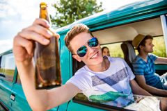 Teenagers inside an old campervan, drinking beer, roadtrip. Teenagers inside an old campervan on a roadtrip, boy leaning out of window, drinking beer, sunny royalty free stock photos