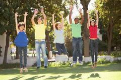Teenagers Jumping In Air In Park Royalty Free Stock Image
