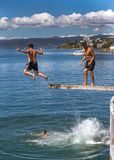 Teenagers jumping off diving board. Wellington, New Zealand - February 11, 2017: Wellington waterfront with teenagers jumping off a diving board near Frank Stock Photography