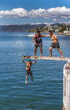 Teenagers jumping off diving board. Wellington, New Zealand - February 11, 2017: Wellington waterfront with teenagers jumping off a diving board near Frank Royalty Free Stock Image