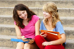 Teenagers laughing at cell phone. Two teenager girls laughing at texto or internet on their cell phone or mobile Stock Photo