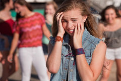 Teenagers Laughing at Scared Girl Stock Photography