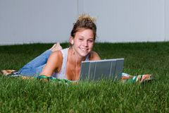 A teenagers lazy Sunday. A young girl relaxing with her mp3 player and laptop stock images