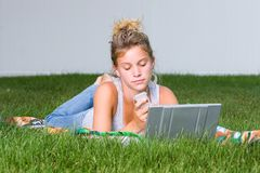 A teenagers lazy Sunday. A young girl relaxing with her mp3 player and laptop stock image