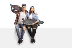 Teenagers with longboards sitting on a panel. Isolated on white background Stock Photos