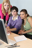 Teenagers looking at a computer Stock Image