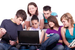 Teenagers looking at laptop Stock Images