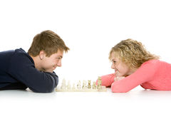 Teenagers lying down playing chess Royalty Free Stock Photos