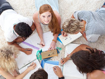 Teenagers lying on the ground studying together royalty free stock photography