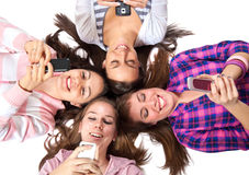 Teenagers lying on white with cellphones smiling Stock Photos