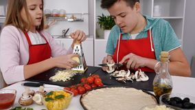 Teenagers making pizza in the kitchen at home. Preparing the ingredients, camera tilt up stock video footage