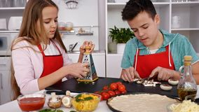 Teenagers making pizza in the kitchen at home. Preparing the ingredients, camera slide stock video footage