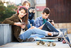 Teenagers with mobile phones. Group of teenagers relaxing with cell phones in the city Royalty Free Stock Images