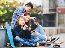 Teenagers with mobile phones. Teenage males and girl relaxing with cell phones in the city Stock Images